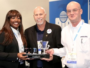 Aubry Baugh, Lumileds, LLC Marketing Communications Manager (left), Ira Davis, Chairman of Import Vehicle Community (Formerly AIA) (center), and Paul Martin, General Manager- LED Solutions, accept the 2015 AIA Award for Best Packaging Design for the Philips X-tremeVision LED Fog Lamp.