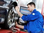 man-in-blue-suit-working-on-wheel-of-car