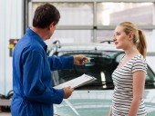 Mechanic discussing car with young woman