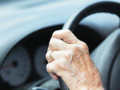 Hand of Senior Man Driver on Car Steering Wheel